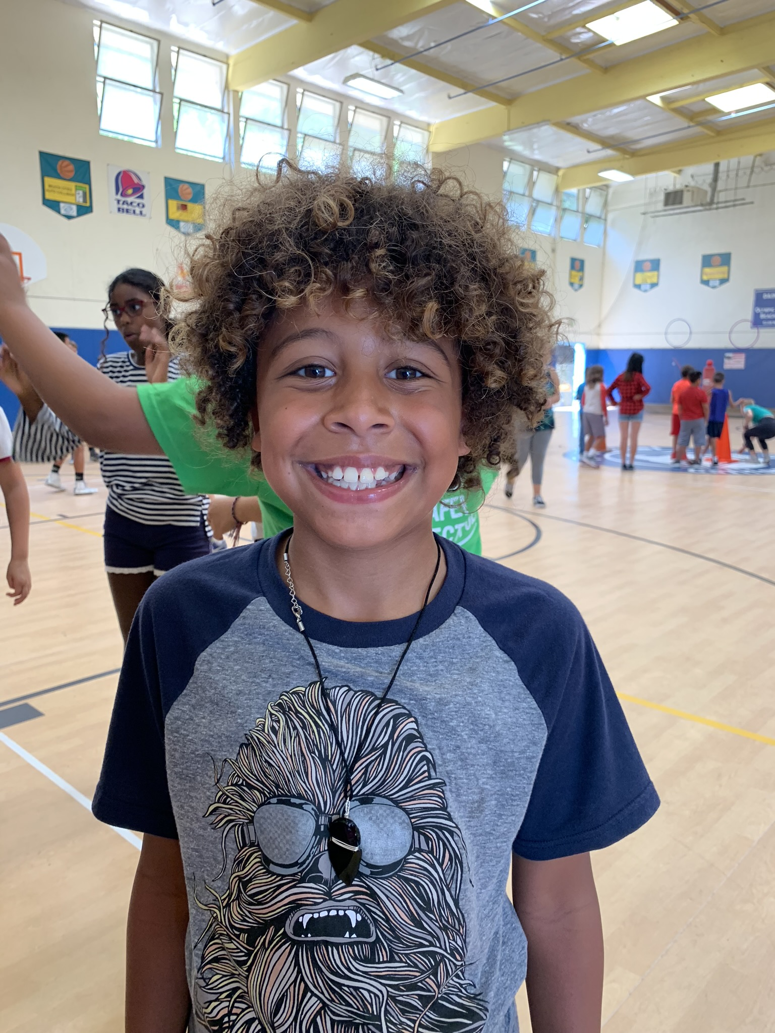 Young boy posing for picture in the Canyon Enrichment Center gym