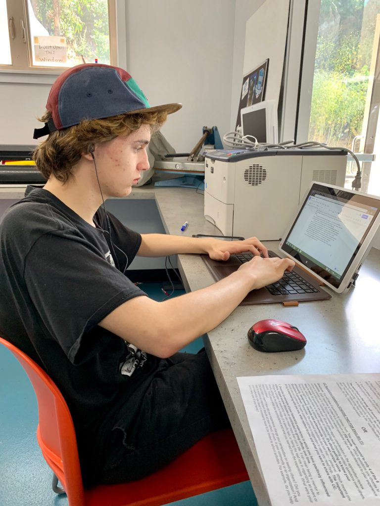 young teen doing homework on ipad computer station at the Canyon Enrichment Center