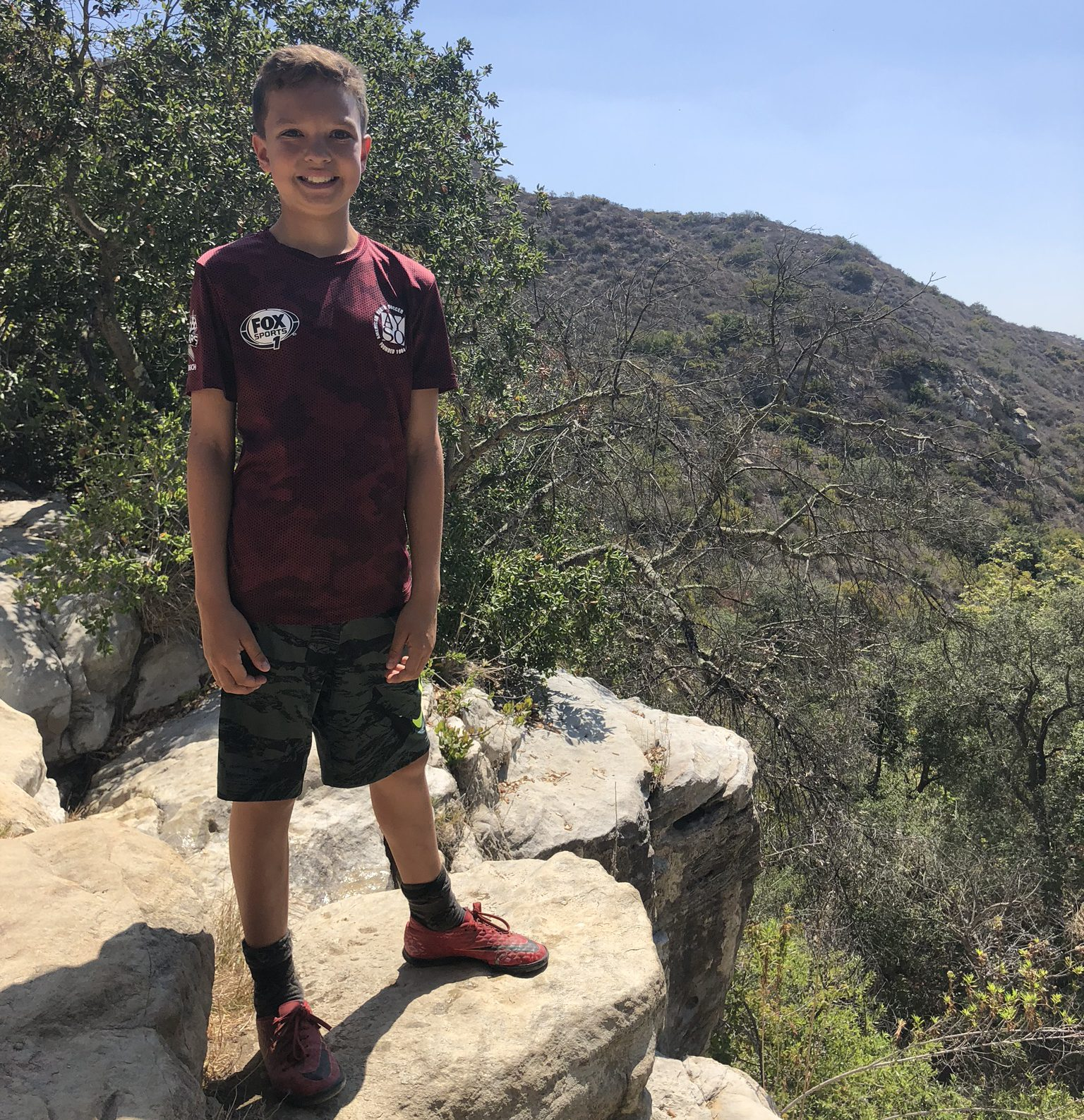 Young Boy on a hike, on top of rocky crest in canyon