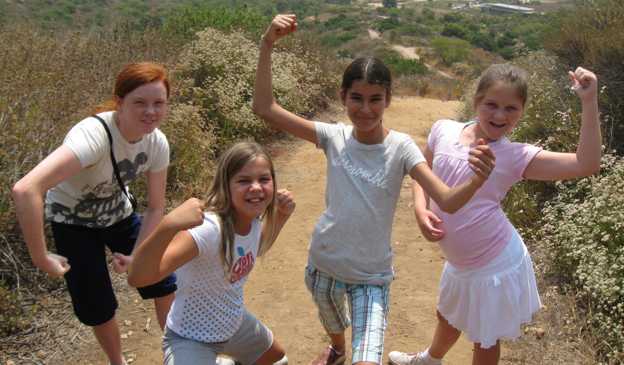 four young girls on a hike in the canyon showing their muscles