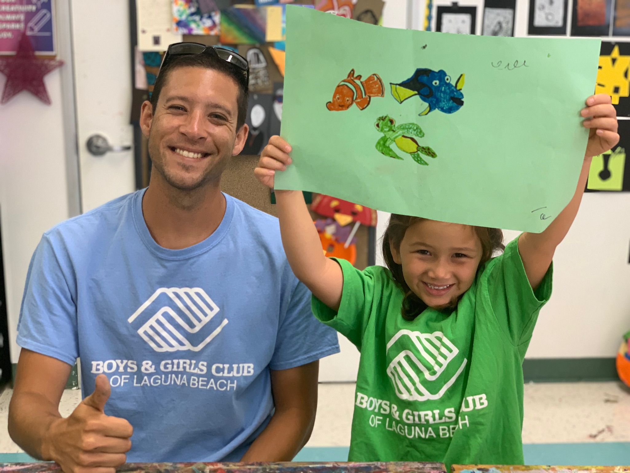 thumbs up from male program volunteer with young girl showing off her artwork