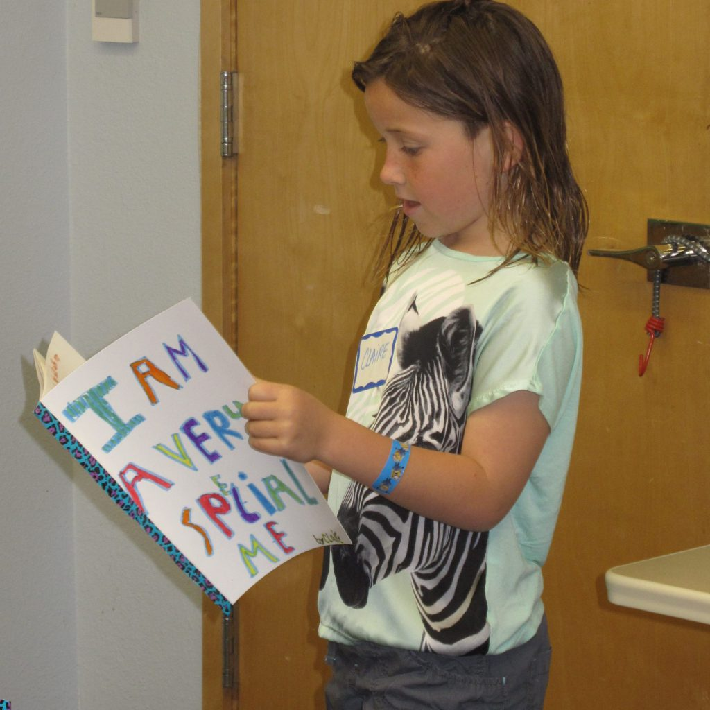 "young girl reading her self made ""I Am A Very Special Me"" book"