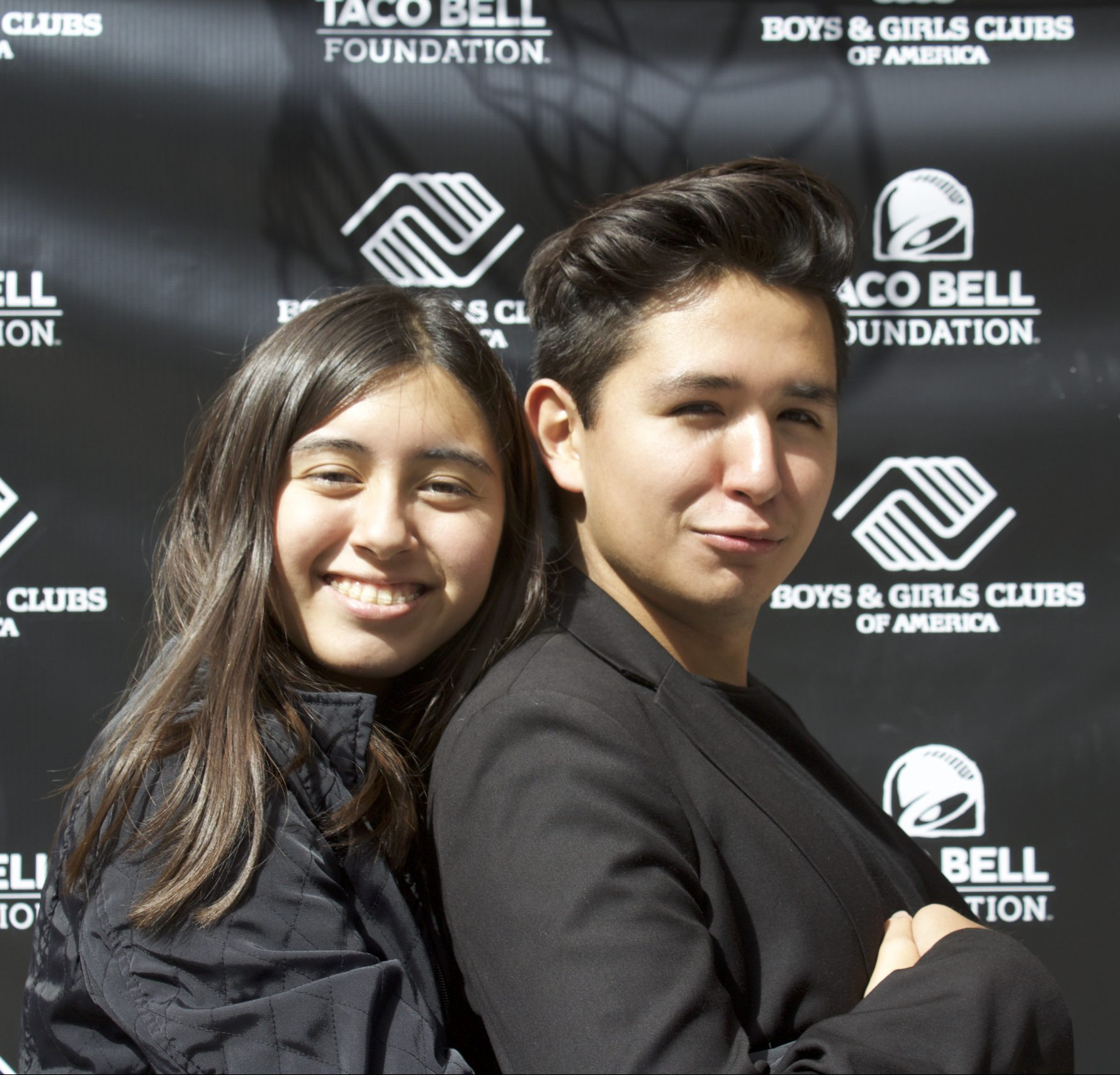 boy and girl in front of event logo backdrop