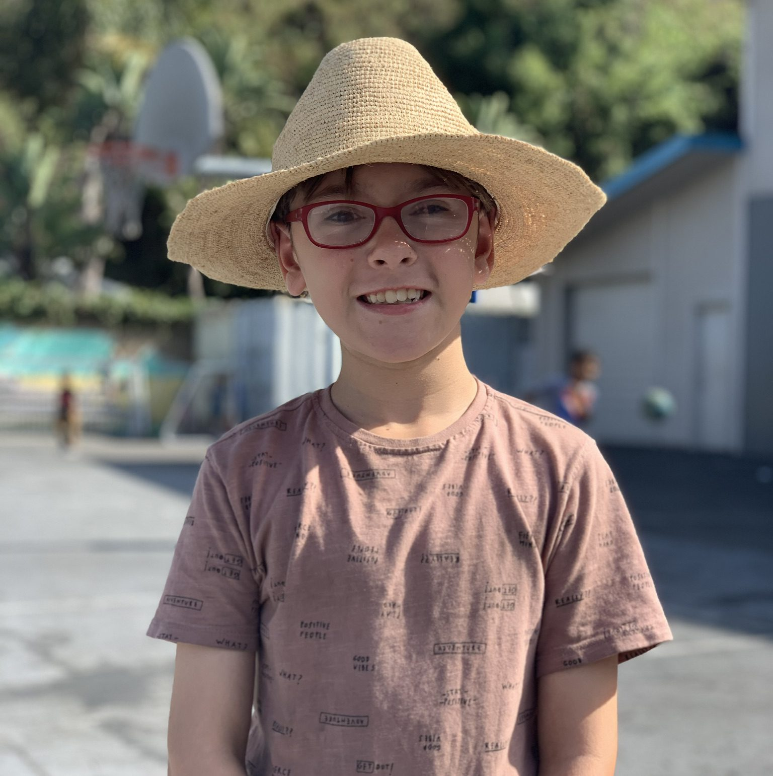 Boy with straw hat on playground at Canyon Enrichment Center