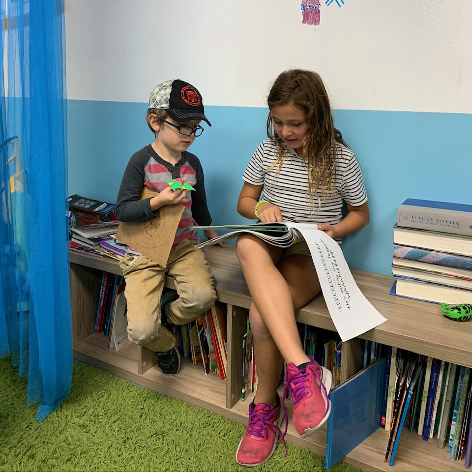 boy and girl sitting on book shelf reading to each other