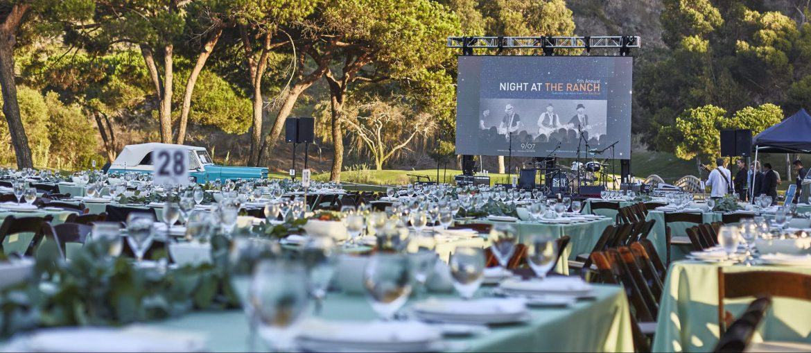 Before arrival–Night at the Ranch outdoor photo of dressed tables with stage backdrop in the background