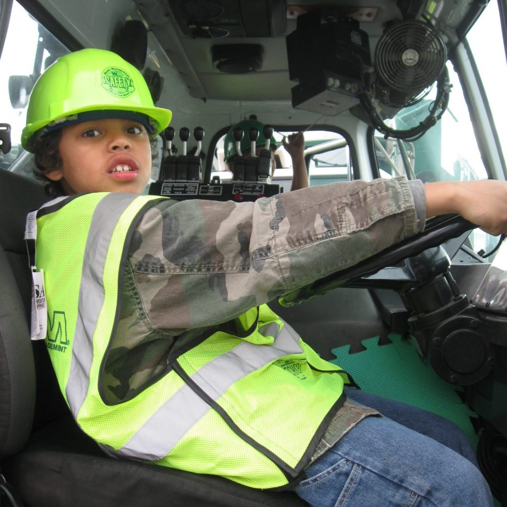young boy in drivers seat of Waste Management truck