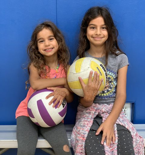 2 girls with volleyballs on bench in gym