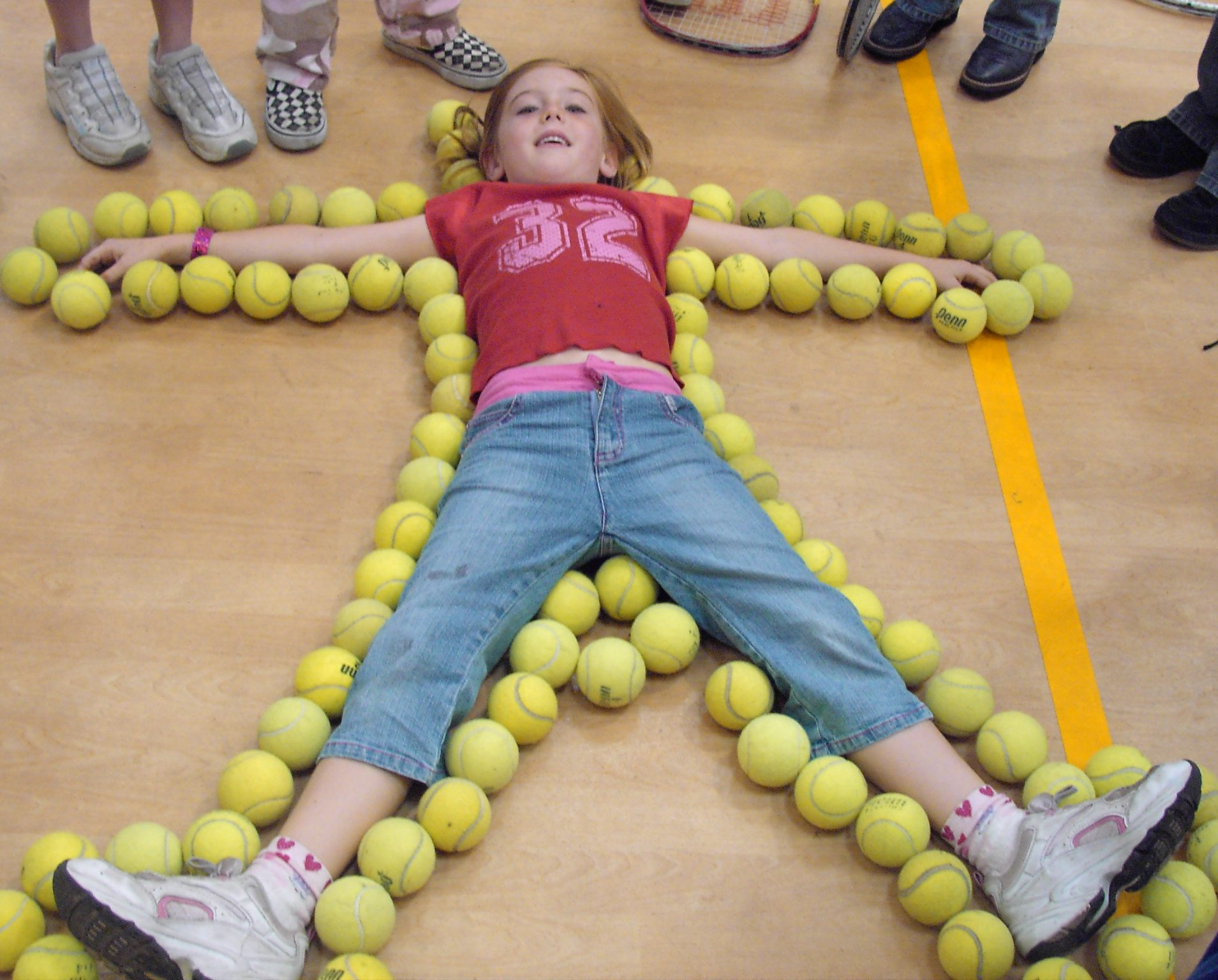 Girl lying flat with arms and legs spread out on floor outlined with tennis balls
