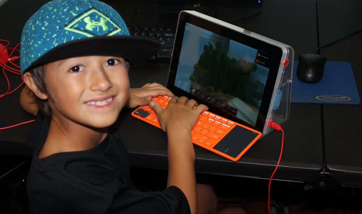 young boy playing a game on a ipad with keyboard
