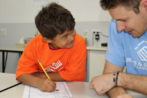 Volunteer helping boy with homework